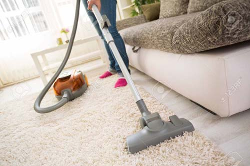 54016383 cleaning carpet with vacuum cleaner in living room